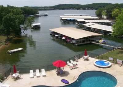 view of pool, lake, and dock from above
