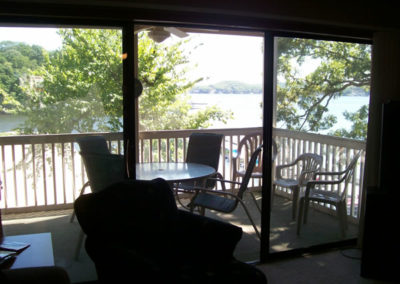 view of deck and lake from living room