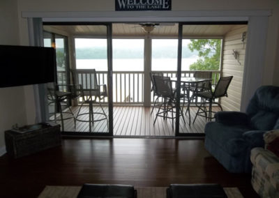view of living room with deck and lake in background