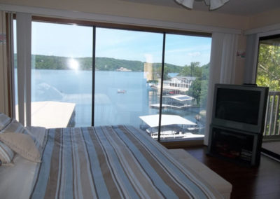 view of lake from bedroom with tv